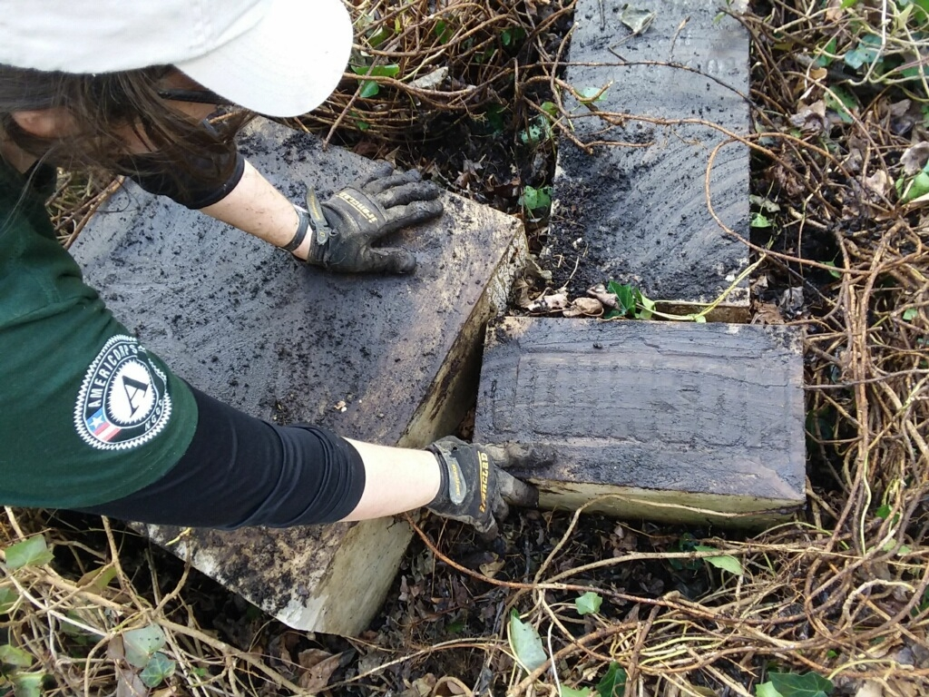 A member of AmeriCorps NCCC Delta 3 clears off a headstone.
