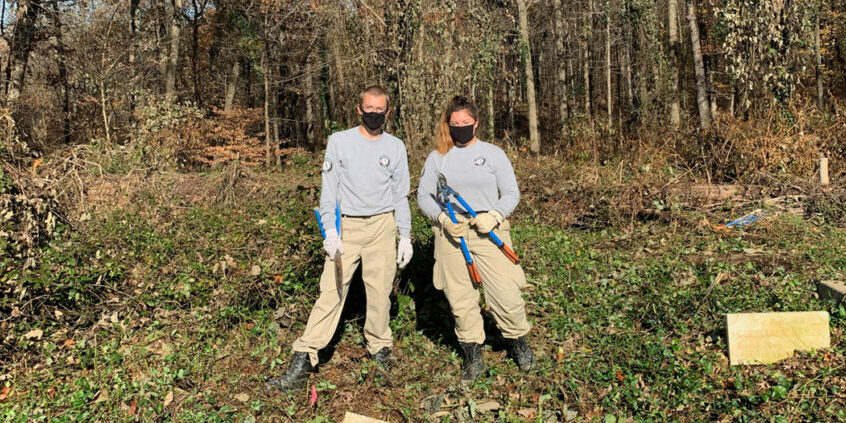 two americorps members working outside